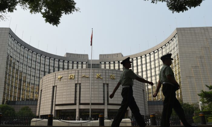 Paramilitary policemen patrol in front of the People's Bank of China in Beijing on July 8, 2015. (Greg Baker/AFP/Getty Images)
