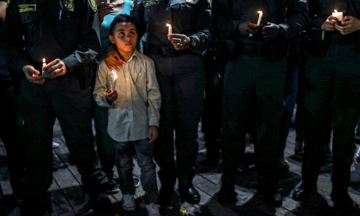 A boy holds a candle next to members of the national police during a tribute to the victims of a car bomb attack in Bogota, Colombia, near Medelin on Jan. 19, 2019. The government has accused the leftist group ELN of carrying out the bombing. (Joaquin Sarmiento     /AFP/Getty Images)
