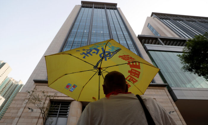 A man holds an umbrella, as forty-four protesters who have been charged with rioting over their actions during a major protest on July 28 are to stand trial at the Eastern Magistrates' Court in Kowloon, Hong Kong, China on Sept. 25, 2019. (Jorge Silva/Reuters)