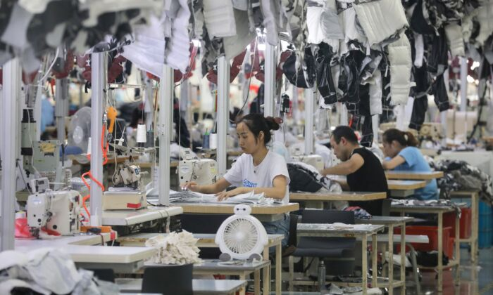 workers are sewing down coats at a factory for Chinese clothing company Bosideng in Nantong of Jiangsu province on September 24, 2019. (STR/AFP/Getty Images)