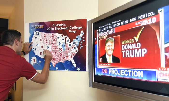 Jake Krupa colors in an electoral map as states projected for Republican presidential candidate Donald Trump or Democratic Presidential candidate Hillary Clinton at an election watching party in Coconut Grove, Fla, on Nov. 8, 2016.  (Rhona Wise/AFP/Getty Images)