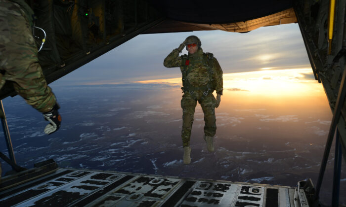 A U.S. Soldier assigned to 1st Battalion, 10th Special Forces Group (Airborne) salutes his fellow Soldiers while jumping out of a C-130 Hercules aircraft over a drop zone in Germany, Feb. 24, 2015. (U.S. Army photo by Visual Information Specialist Jason Johnston/Released)