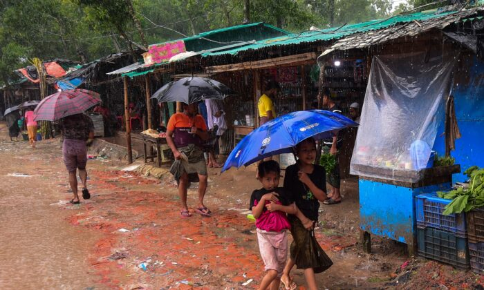Rohingya refugees shelter under umbrellas as they walk through the Kutupalong refugee camp in Ukhia on Sept. 12, 2019. (MUNIR UZ ZAMAN/AFP/Getty Images)
