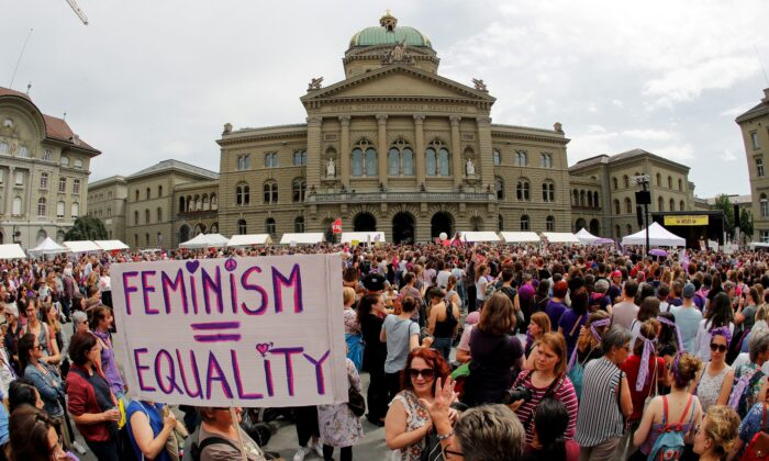 """A woman holds a sign reading """"Feminism = Equality"""" as she takes part in a nation-wide women's strike for wage parity outside the federal palace, on June 14, 2019 in the Swiss capital Bern. (Stefan Wermuth/AFP/Getty Images)"""