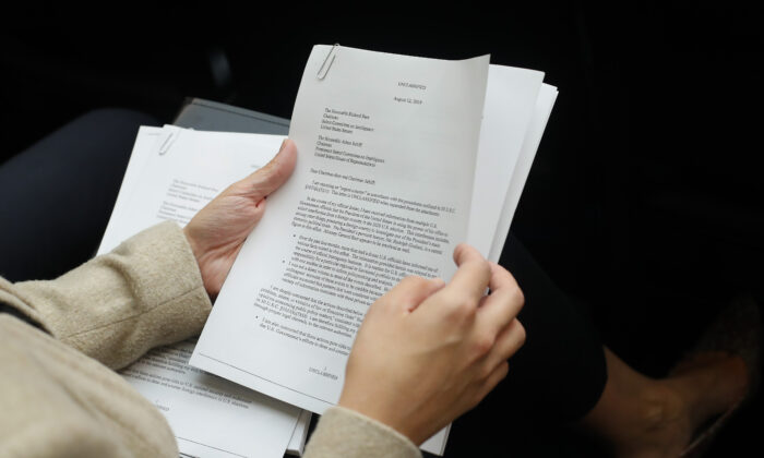 A member of the audience holds a copy of the Whistle-Blower Complaint letter sent to Senate and House Intelligence Committees during testimony by Acting Director of National Intelligence Joseph Maguire before the House Intelligence Committee on Capitol Hill in Washington on Sept. 26, 2019. (Pablo Martinez Monsivais/AP Photo)