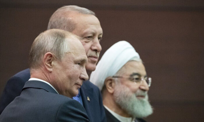 Russian President Vladimir Putin (L), Turkish President Recep Tayyip Erdogan and Iranian President Hassan Rouhani (R) pose for a picture after a news conference during their meeting in Ankara, Turkey, on Sept. 16, 2019. (Pavel Golovkin/AP Photo)