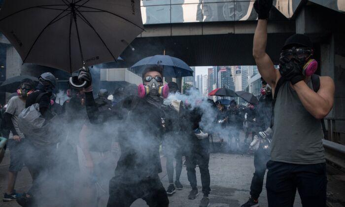 Pro-demokratické protesty v Hongkongu. Střet demonstrantů s policií, která vystřeluje slzný plyn během pochodu v Hongkongu 29. září 2019. (Chris McGrath / Getty Images)