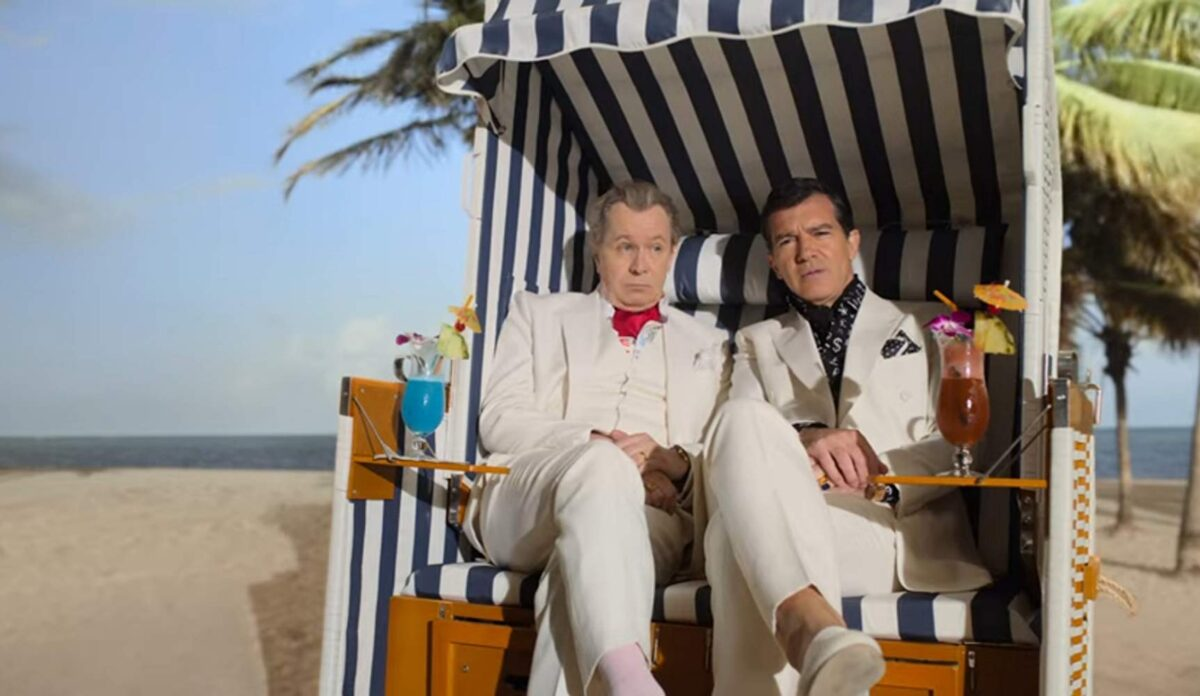 two men in white suits on a beach