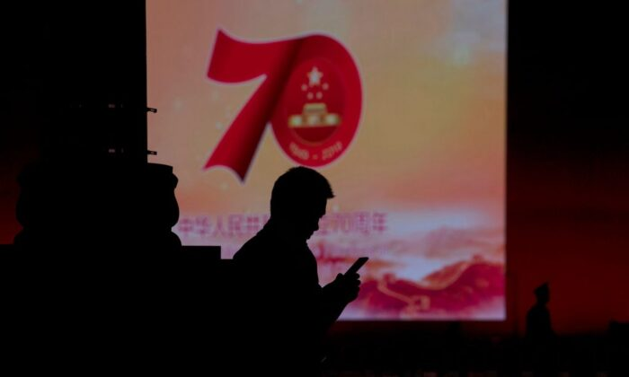 A man uses his mobile phone in front of a screen that shows a message about the 70th anniversary of the founding of the Chinese communist regime, in Beijing on Sept. 26, 2019. (Noel Celis/AFP/Getty Images)