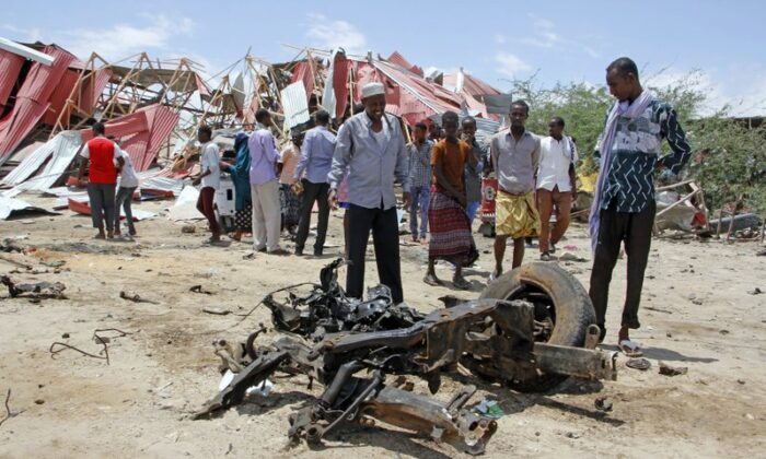 Somalis watch the wreckage of the car bomb after an attack on a European Union military convoy in the capital Mogadishu, Somalia on Sept. 30, 2019. (Farah Abdi Warsameh/AP Photo)