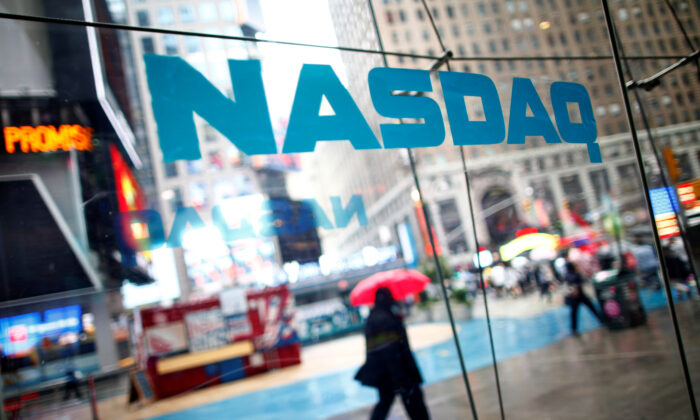 People walk past the NASDAQ MarketSite in New York's Times Square, U.S. on June 4, 2012. (Eric Thayer/Reuters)