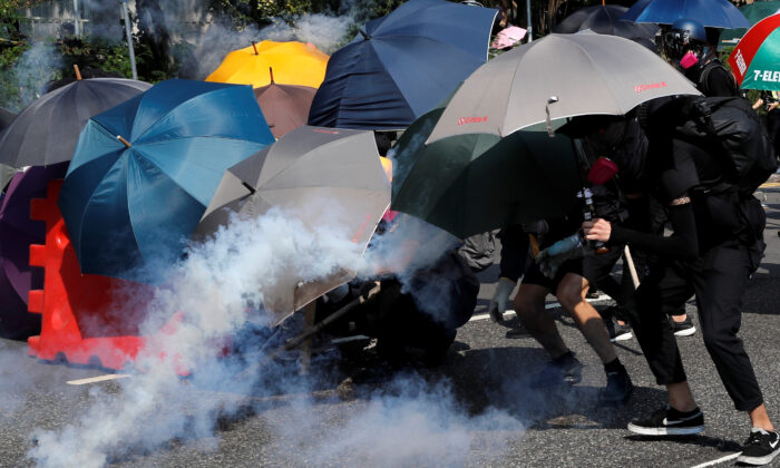Protesters cover themselves with umbrellas during a protest in Wong Tai Sin, Hong Kong, on Oct. 1, 2019. (Tyrone Siu/Reuters)