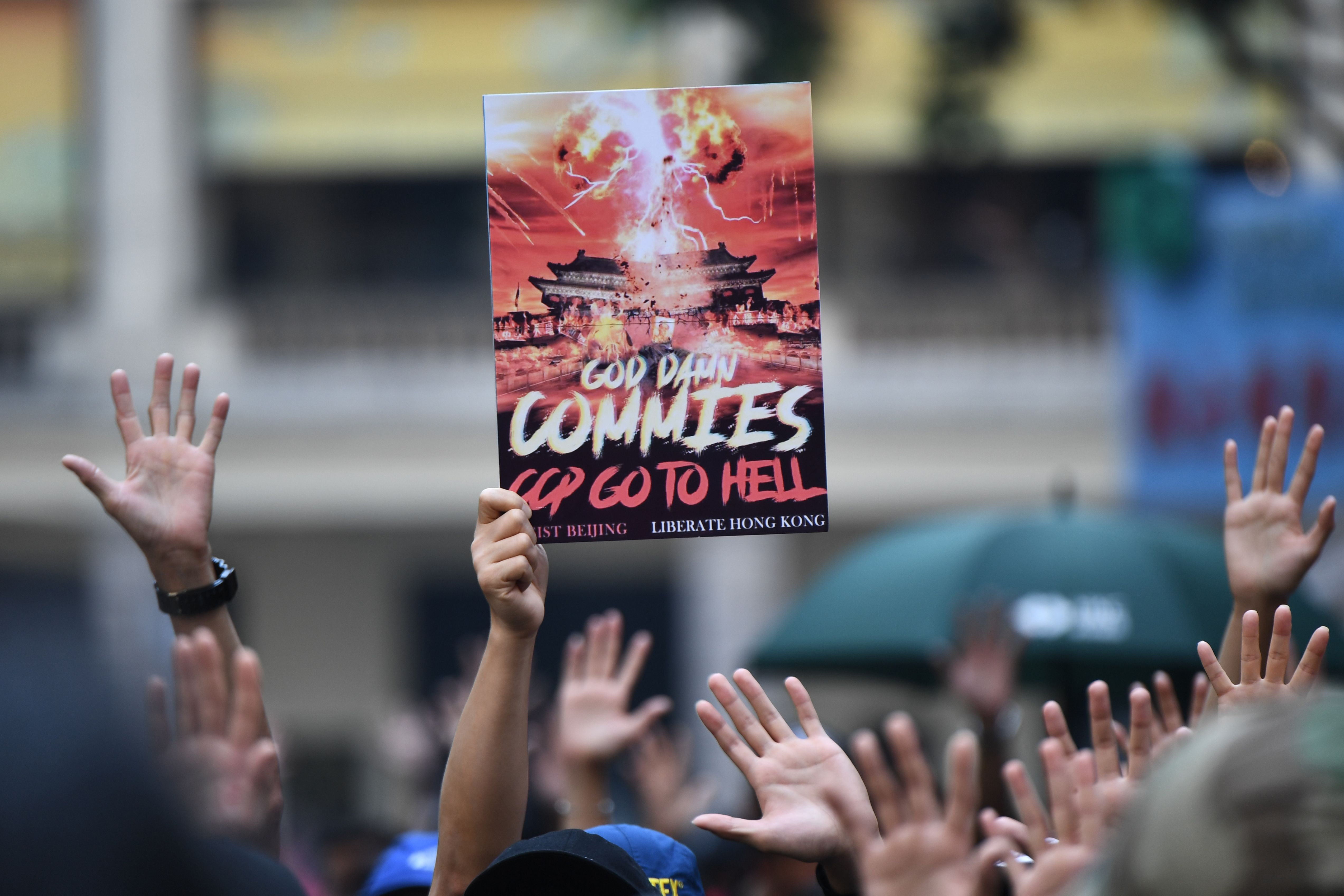 A protester holds up a placard as others hold up their hands to signify their five demands at a rally in the Wanchai district of Hong Kong.