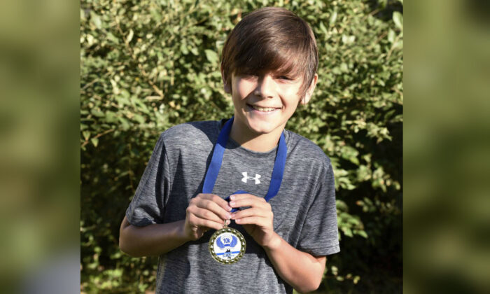 Kade Lovell, 9, smiles with his medal for winning the St. Francis Xavier Franny Flyer 10k on Saturday, Sept. 28, 2019 in Sartell, Minn. (Zach Dwyer/The St. Cloud Times via AP)