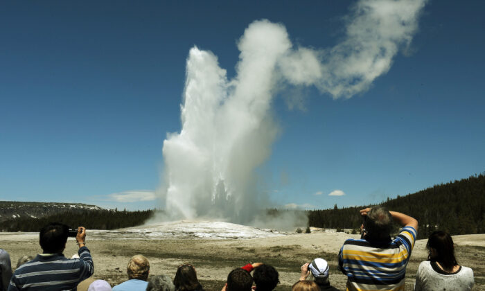 Tourists watch the 'Old Faithful' geyser in the Yellowstone National Park, Wyoming, on June 1, 2011.  (Mark Ralston/AFP/Getty Images)