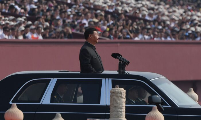 Chinese regime leader Xi Jinping begins a review of troops from a car during a military parade at Tiananmen Square in Beijing on Oct. 1, 2019. (GREG BAKER/AFP/Getty Images)