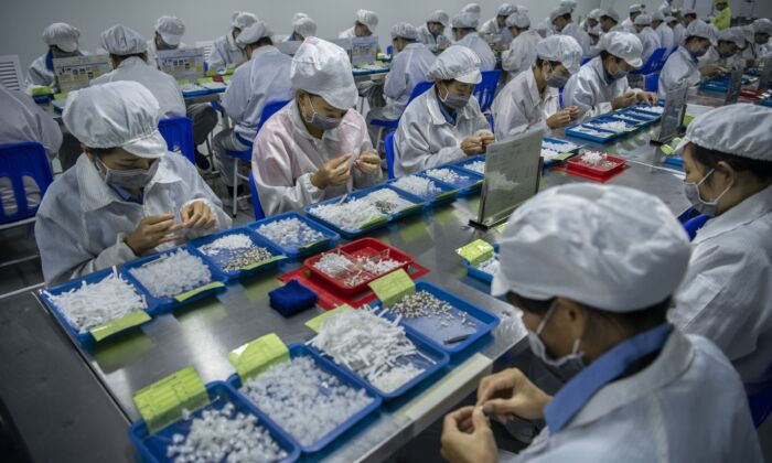 Workers assemble parts for e-cigarettes on the production line at KangerTech, one of China's leading manufacturers of vaping products in Shenzhen, China on September 24, 2019. (Kevin Frayer/Getty Images)