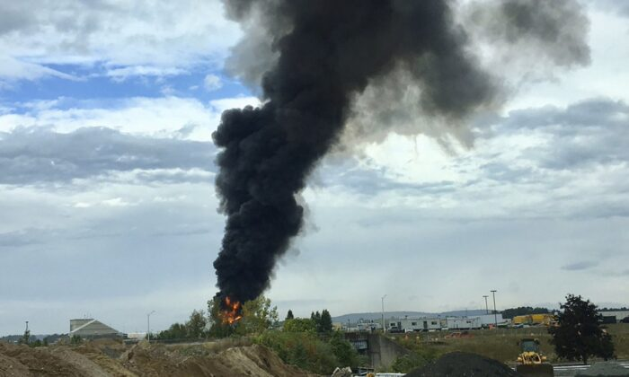 Smoke fills the sky after a World War II-era bomber plane crashed outside Bradley International Airport north of Hartford, Conn. A spokesman for Gov. Ned Lamont confirmed the crash of the B-17 plane on Oct. 2, 2019.  (Antonio Arreguin via AP)