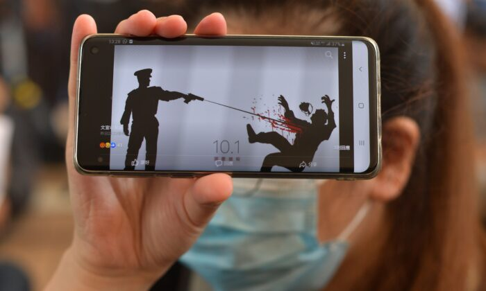 A woman holds up her phone showing an image of the police shooting of the young protester outside the entrance to the West Kowloon Court in Hong Kong on Oct. 2, 2019. (Nicolas Asfouri/AFP via Getty Images)