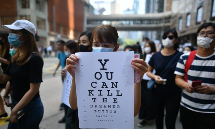 "A protester holds a placard, mimicking an eye chart that reads ""you can kill the dreamer but you can't kill the dream,"" during a rally at Chater Garden, Hong Kong on Oct. 2, 2019. (Mohd Rasfan/AFP via Getty Images)"