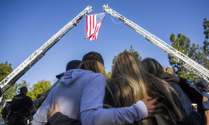 Friends hug outside the Los Robles Medical Center in Thousands Oaks, California on Nov. 8, 2018, as they pay tribute to Ventura County Sheriff Sgt. Ron Helus who was killed in a shooting at Borderline Bar the night before. (Apu Gomes/AFP/Getty Images)