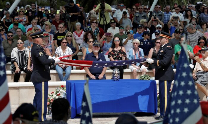 An honor guard folds an American flag during an open funeral service for U.S. Army veteran Edward K. Pearson, on Oct. 1, 2019, at the Sarasota National Cemetary in Sarasota, Fla. Pearson has no family so his funeral home sent out a request on social media for the public to attend the service. (AP Photo/Chris O'Meara)