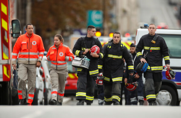 French police and firefighters are seen in front of the Paris Police headquarters in Paris