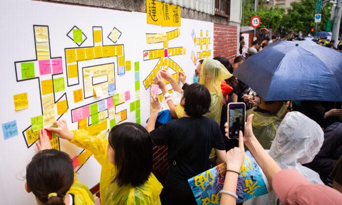 People put up Post-it notes on a Lennon Wall in Taipei, Taiwan on Sept. 29, 2019. (Chen Po-chou/The Epoch Times)