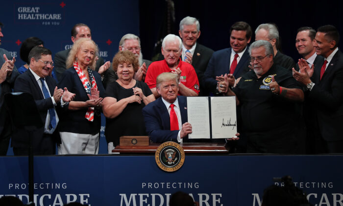 President Donald Trump signs an executive order concerning Medicare during an event at the Sharon L. Morse Performing Arts Center on Oct. 03, 2019 in The Villages, Florida. (Joe Raedle/Getty Images)