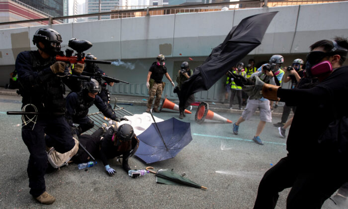 A riot police officer fires pepper-spray projectile toward protesters demonstrating near the Legislative Council building in Hong Kong, China on Sep. 29, 2019. (Athit Perawongmetha/Reuters)