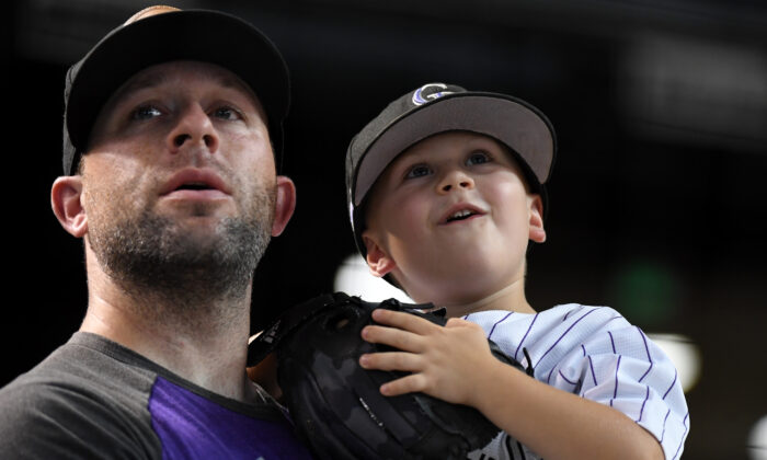 A father and son watch batting practice prior to a game between the Colorado Rockies and Arizona Diamondbacks at Chase Field in Phoenix, Ariz., on Aug. 20, 2019. (Norm Hall/Getty Images)