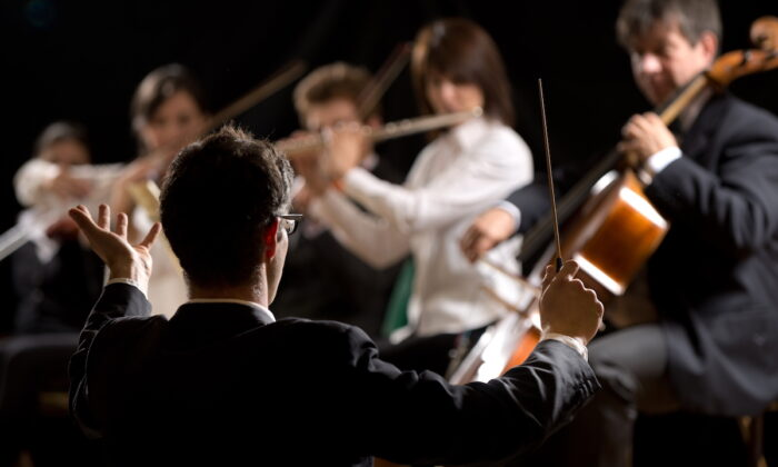 The conductor's role is to communicate with the performers and their audience. Their role is part artistic, part mathematical. (Shutterstock)