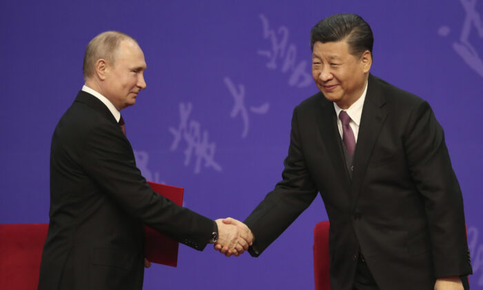 Russian President Vladimir Putin shakes hands with Chinese leader Xi Jinping during the Tsinghua University ceremony in Beijing, China  on April 26, 2019. (Kenzaburo Fukuhara - Pool/Getty Images)