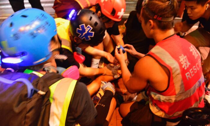 Medics surround the injured protester in Yuen Long, Hong Kong, on Oct. 4. (Yu Tianyou/The Epoch Times)