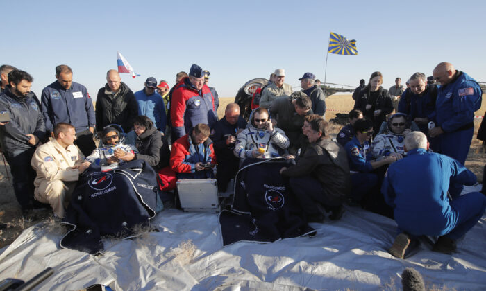 U.S. astronaut Nick Hague, right, Russian cosmonaut Alexey Ovchinin, centre, and United Arab Emirates astronaut Hazzaa Ali Almansoori, sit in chairs shortly after the landing of the Russian Soyuz MS-12 space capsule about 150 km ( 90 miles) south-east of the Kazakh town of Zhezkazgan Kazakhstan on Oct. 3, 2019. (Dmitri Lovetsky/AP)