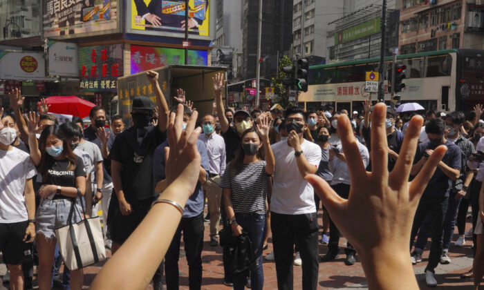 Protesters wear masks and hold up their hands to represent their five demands in Hong Kong on Oct. 4, 2019. (Vincent Yu/AP)
