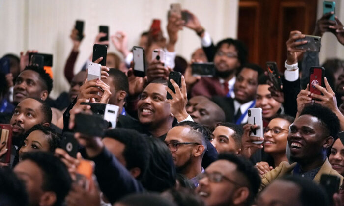 Guests cheer for President Donald Trump as he arrives at an event for the Young Black Leadership Summit in the East Room of the White House in Washington, on Oct. 4, 2019. (Chip Somodevilla/Getty Images)