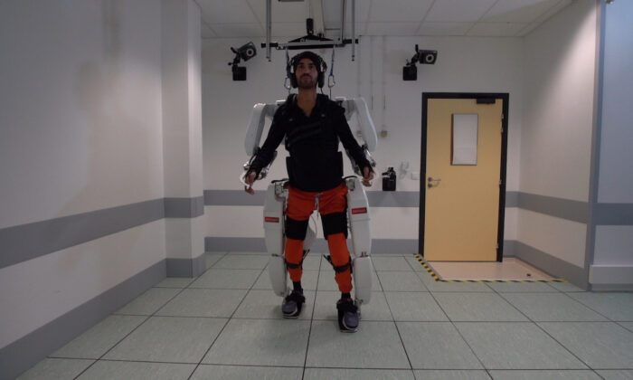 A patient with tetraplegia walks using an exoskeleton in Grenoble, France, in Feb. 2019. (Fonds De Dotation Clinatec/La Breche/Handout via Reuters)