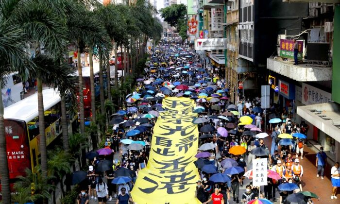 "Protesters walk next to a banner with the words ""May Glory return to Hong Kong"" in Hong Kong on Oct. 5, 2019. (AP Photo/Vincent Thian)"