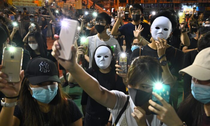 People wear masks and light up their mobile phones during a flash mob rally in the Sham Shui Po district in Hong Kong on Oct. 5, 2019. (Philip Fong/AFP/Getty Images)