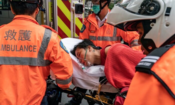 A pedestrian is lifted into an ambulance after inhaling tear gas in Wan Chai district in Hong Kong on October 6, 2019. (Anthony Kwan/Getty Images)