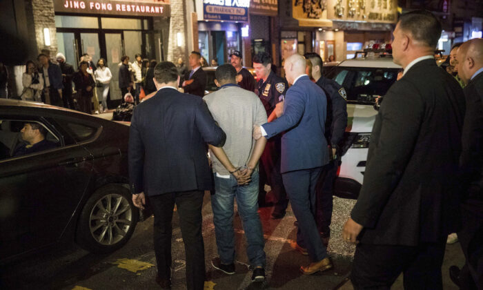 Police officers escort Randy Rodriguez Santos from the 5th Precinct to a vehicle bound for a hospital for evidence collection, in New York City on Oct. 5, 2019. (Julius Constantine Motal/(AP Photo)
