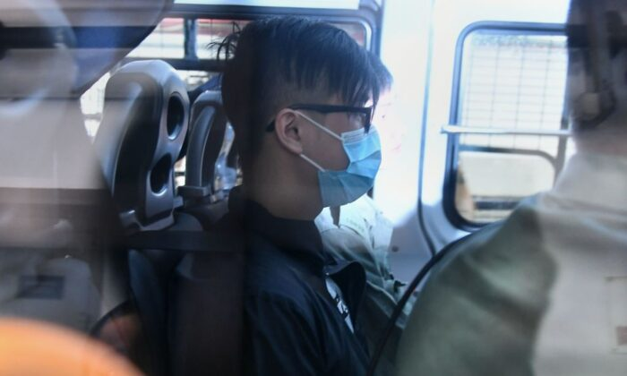 A man (C) wearing a face mask arrives in a police vehicle to the Eastern District Courts in Hong Kong on Oct. 7, 2019, where the first protesters arrested for wearing face masks appeared in court. (Mohd Rasfan/AFP via Getty Images)