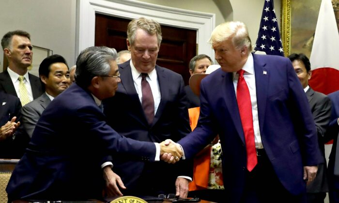 President Donald Trump shakes hands with Japanese Ambassador to the United States Shinsuke Sugiyama (L) and U.S. Trade Representative Robert Lighthizer after they signed a trade agreement in the Roosevelt Room of the White House on Oct. 7, 2019. (Evan Vucci/AP Photo)
