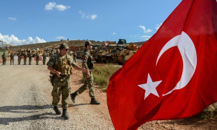 Turkish soldiers stand near armored vehicles as a man waves a Turkish national flag during a demonstration in support of the Turkish army's Idlib operation near the Turkey-Syria border near Reyhanli, Hatay, on Oct. 10, 2017.  (Ilyas Akenga/AFP/Getty Images)