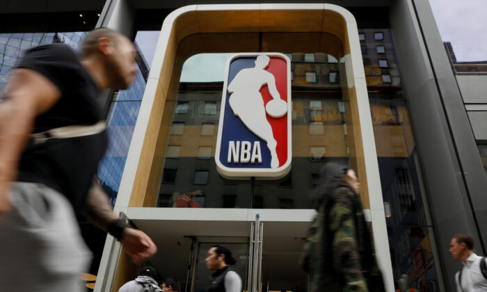 The NBA logo is displayed as people pass by the NBA Store in New York, N.Y., on Oct. 7, 2019. (Brendan McDermid/Reuters)