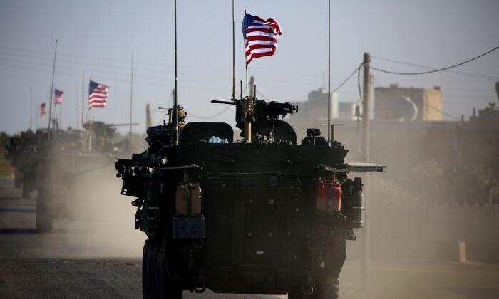 A convoy of United States forces armoured vehicles drives near the village of Yalanli, on the western outskirts of the northern Syrian city of Manbij, in a 2017 file photograph. (Deliil Souleiman/AFP/Getty Images)