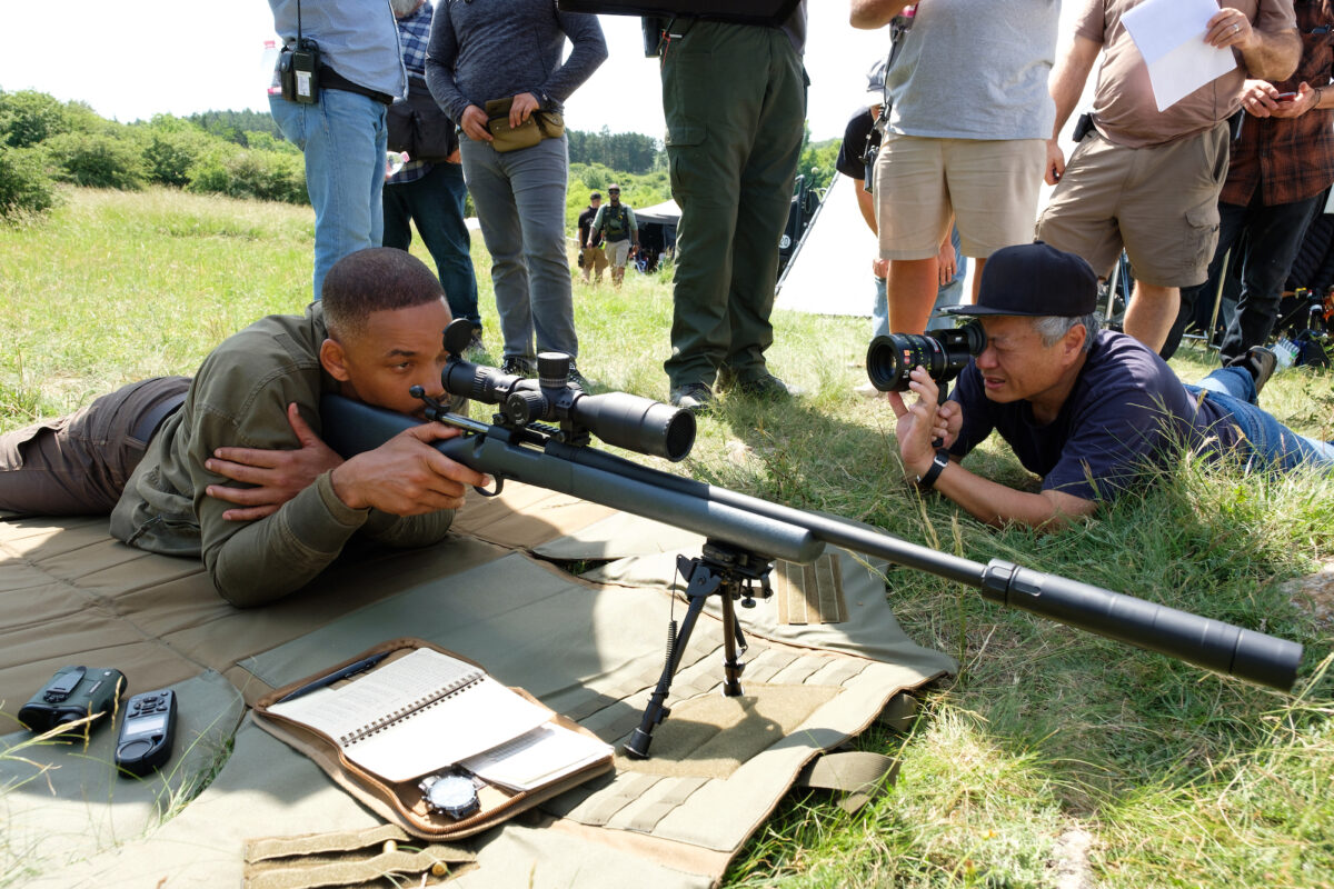 Actor with sniper rifle director with camera
