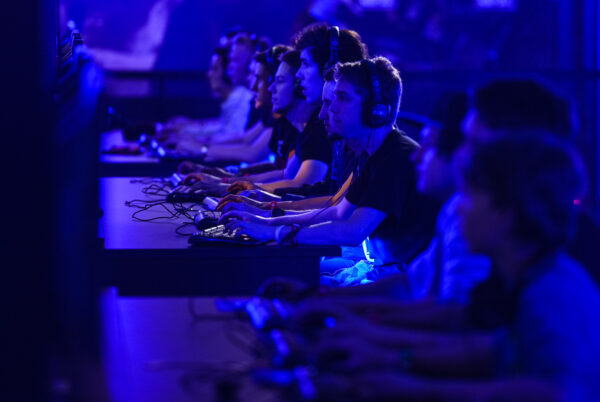 Visitors try out games at the Blizzard Entertainment stand at the Gamescom 2015 gaming trade fair in Cologne, Germany.