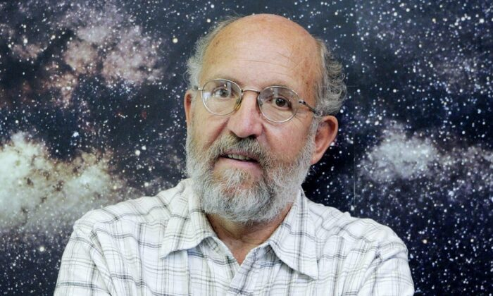 Swiss professor Michel Mayor, astrophysicist and director of the Geneva Observatory, poses in front of the picture of the Milky Way, in Geneva, Switzerland on May 17, 2006. (Salvatore Di Nolfi, Keystone via AP)